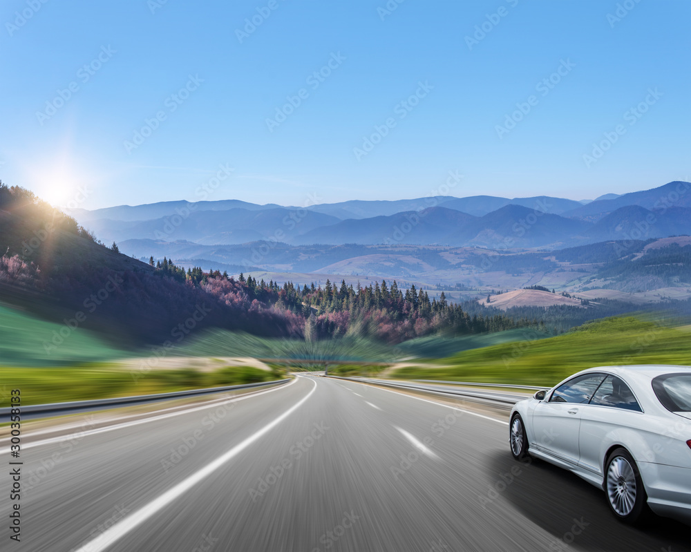 Fototapety, obrazy: White car moves on the road among the mountains and forests.