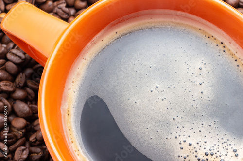 Wall Murals Cafe Part of the orange cup with coffe on coffee beans background