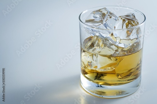 Foto auf Leinwand Alkohol Closeup shot of a glass full of ice and some whiskey isolated on a white background