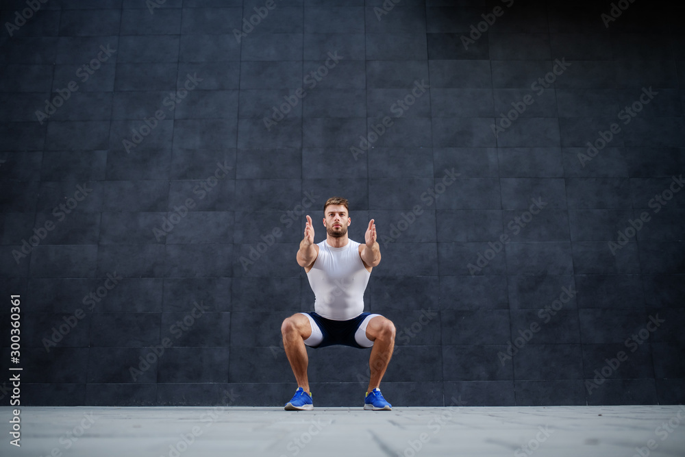 Fototapeta Handsome muscular caucasian man in shorts and t-shirt doing squatting exercise outdoors. In background is gray wall.