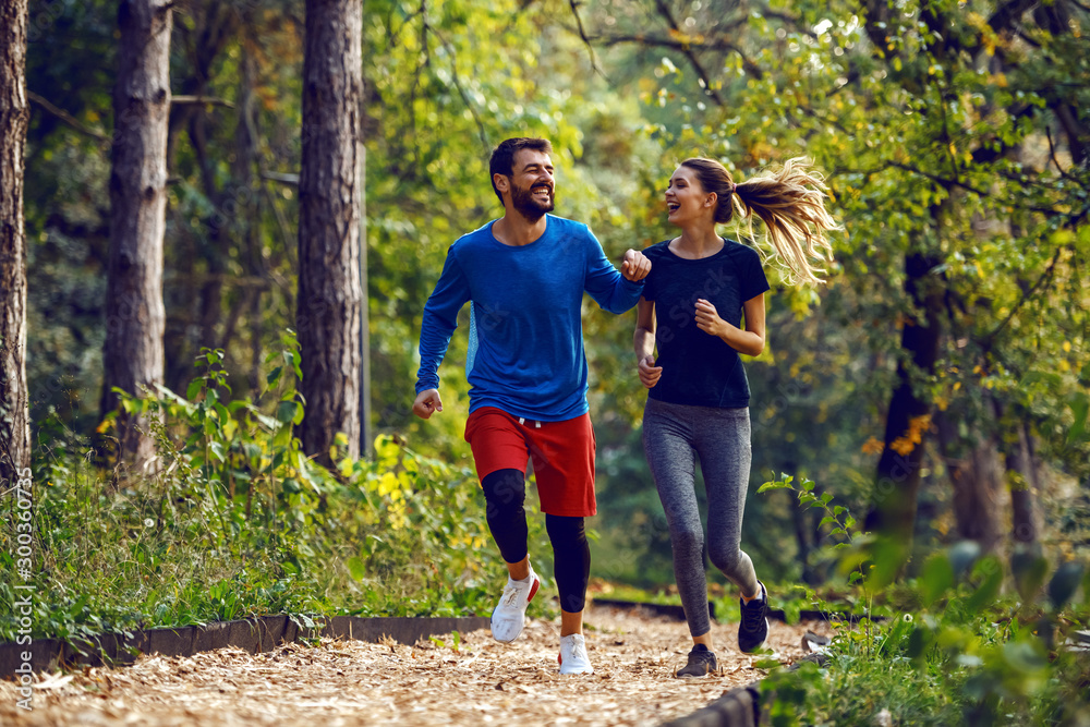 Fototapeta Full length of fit sporty happy caucasian couple in sportswear running in woods on trail in morning.