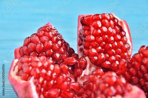 Ripe pomegranate fruit with selective focus on blue wooden background. beautiful red pomegranate on textured turquoise backdrop. Ripe organic pomegranate for healthy food