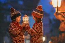 Beautiful Children, Boy Brothers Holding Lantern, Casually Dressed, Looking At Night View Of Prague City