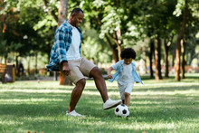 Happy African American Man Playing Football With Curly Son