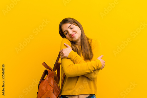 Fotomural young pretty woman feeling in love, smiling, cuddling and hugging self, staying