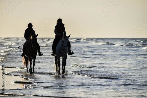 two horse riders on the beach under a beautiful sunset Wallpaper Mural
