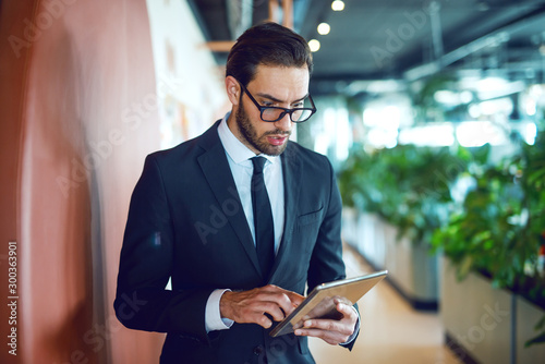 Valokuva  Stunned handsome caucasian businessman in suit and with eyeglasses using tablet while standing in hallway at corporate company