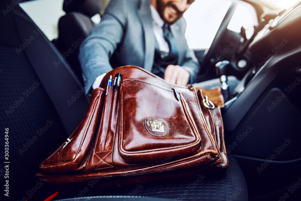 Fototapety, obrazy: Businessman sitting in his car and taking out something from his briefcase. Selective focus on briefcase.