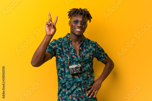 Young black rasta man wearing a vacation look joyful and carefree showing a peace symbol with fingers Canvas-taulu