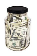 A Hundred US Dollars Bank Notes In A Glass Jar With Black Cap Isolated On White Background