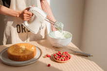 Male Hands Whipping Whites Cream In Glass Bowl With Mixer On Wooden Table. Making Sponge Cake Or Red Velvet Cake