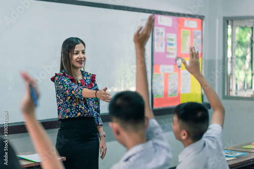 Fotomural  An smiling Asian female high school teacher teaches the white uniform students in the classroom by asking questions and then the students raise their hands for answers