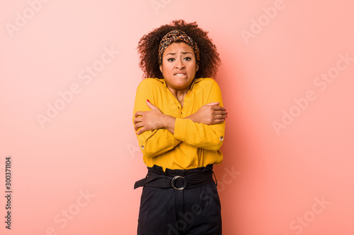 Young african american woman against a pink background going cold due to low temperature or a sickness Fototapeta