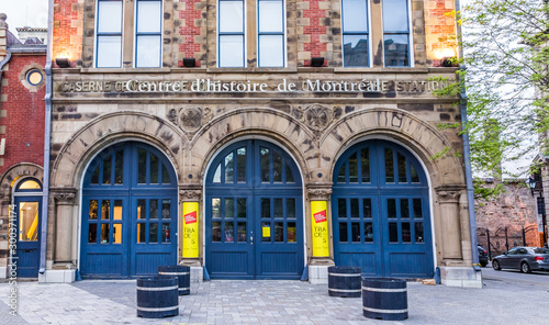 Montreal, Canada - May 27, 2017: Old town area brick building illuminated by yellow lights and lanterns called center of history by street in evening outside in Quebec region city