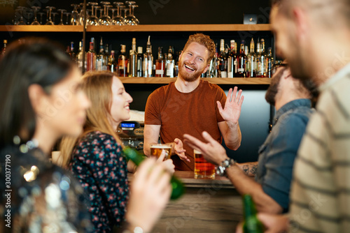Photo Handsome caucasian bartender giving beer on house to customers.