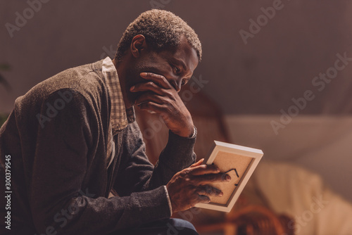 Fotografie, Obraz senior, depressed african american man looking at photo frame