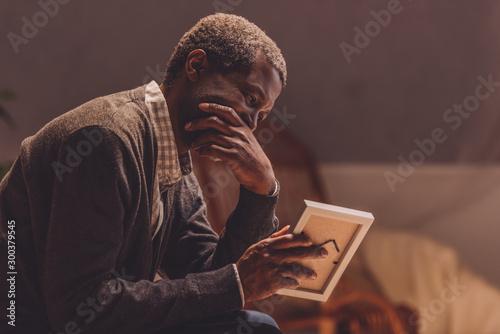 Fotografie, Obraz  senior, depressed african american man looking at photo frame
