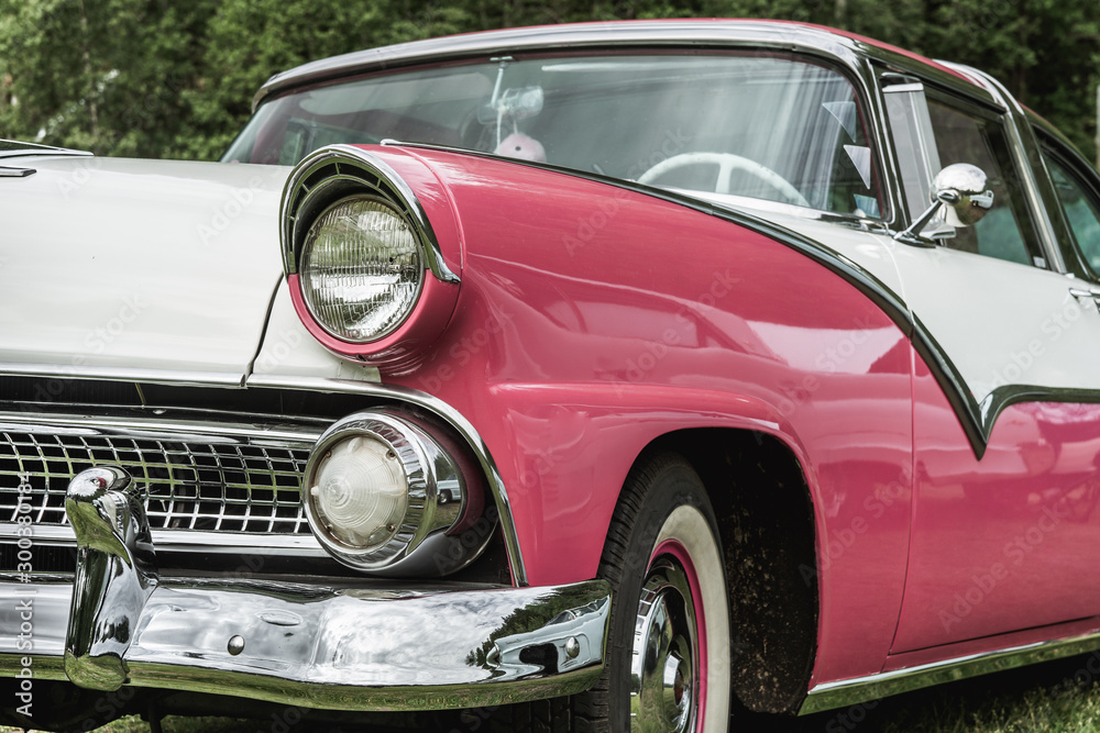 Fototapeta Partial front view of pink and white classic car from the fifties