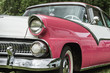 Partial front view of pink and white classic car from the fifties