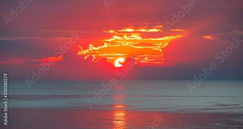 Fototapeta Amazing sunrise over the sea with through the clouds  obraz