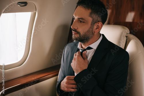 Fototapeta bearded businessman touching tie and sitting in plane obraz