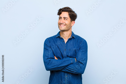 Photo young handsome man feeling happy, proud and hopeful, wondering or thinking, look