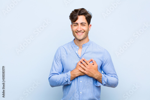 Fototapeta young handsome man feeling romantic, happy and in love, smiling cheerfully and h