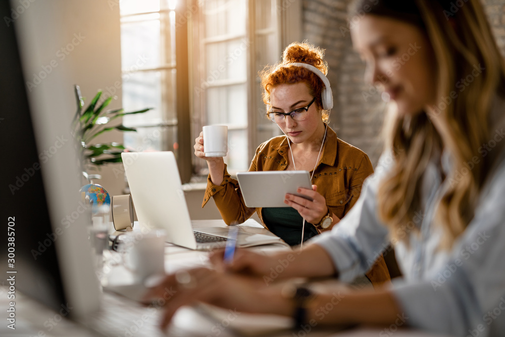 Fototapeta Young redhead businesswoman using touchpad while drinking coffee in the office.