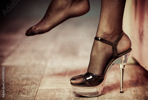 sexy feet in stockings and high heel closeup on wooden floor