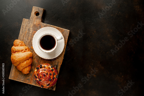Obraz Coffee and croissant, bun on a stone table. morning breakfast, with copy space for text - fototapety do salonu