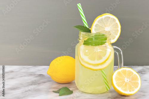 Lemon lemonade in mason jar glass ofwith lemons and straw on tab