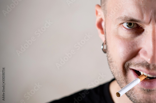 Fototapeta a man with a stern face is about to light a cigarette. copy space