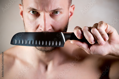 Fotografia, Obraz  stern man closes his mouth with a kitchen knife