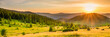 Leinwandbild Motiv Panorama of sunset in the mountains with forest, green grass and big shining sun on dramatic sky