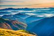 Leinwandbild Motiv Sunset in beautiful blue mountains and mist hills