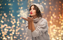 Christmas, Season And People Concept - Happy Young Woman In Knitted Winter Hat And Sweater Sending Air Kiss Over Festive Lights Background