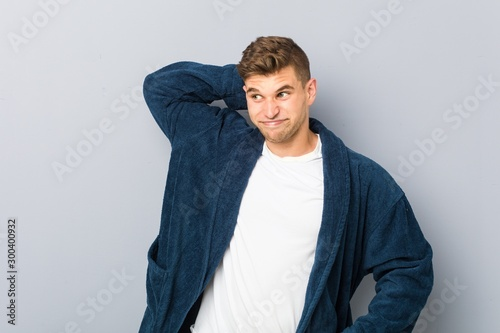 Obraz na plátně  Young caucasian man wearing pajama touching back of head, thinking and making a choice