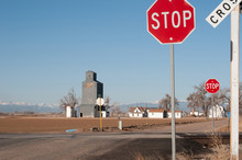 Dirt Road With A Railroad Crossing Controled With Stop Signs.