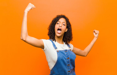 young pretty black woman shouting triumphantly, looking like excited, happy and surprised winner, celebrating against orange wall