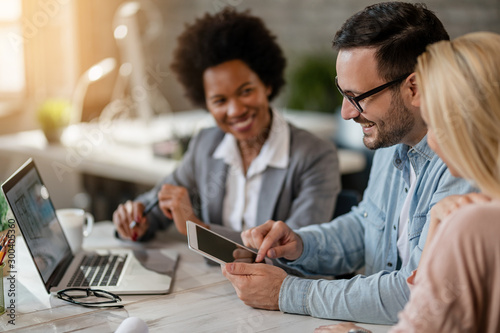 Happy couple using touchpad on a meeting with real estate agent.