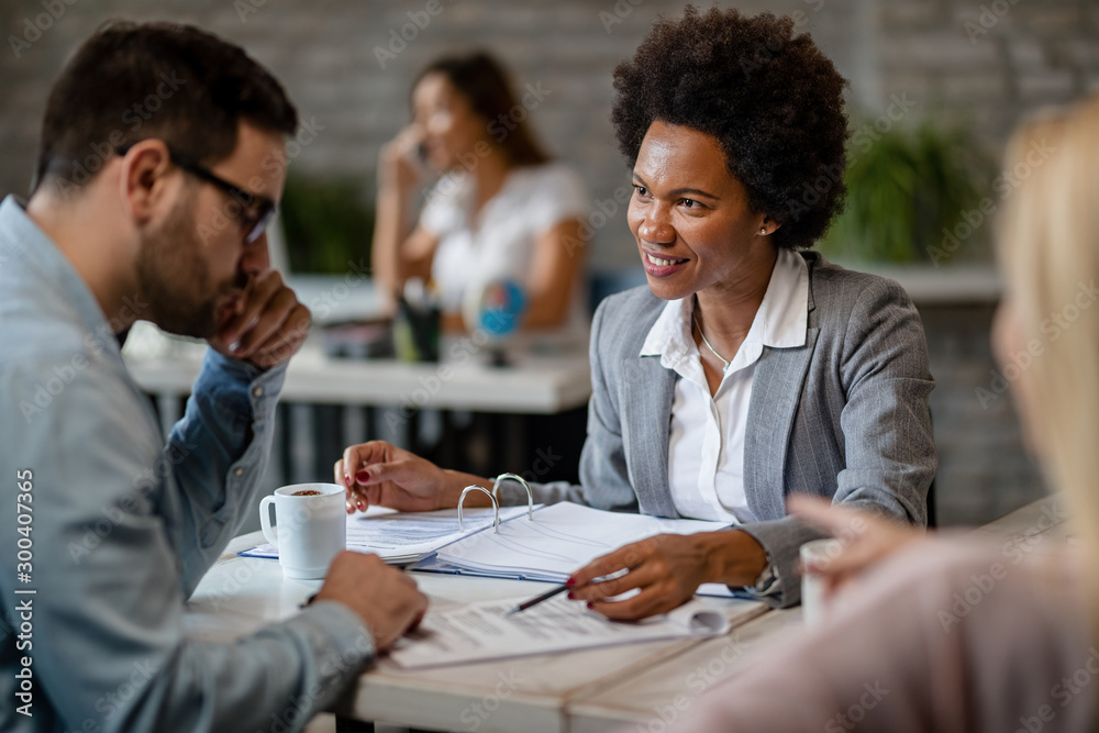 Fototapeta Happy African American financial advisor having consultations with clients in the office.