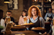 canvas print picture - Young happy waitress serving her guest in a pub.