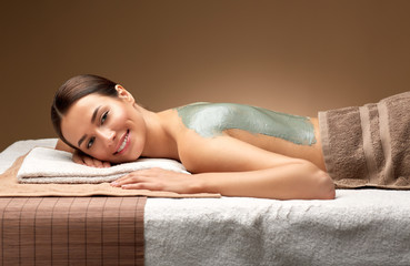 wellness, beauty and cosmetology concept - beautiful young woman lying with blue clay mask on back at spa