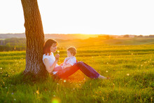 Young Mother With Little Baby Boy Sitting At Sunset