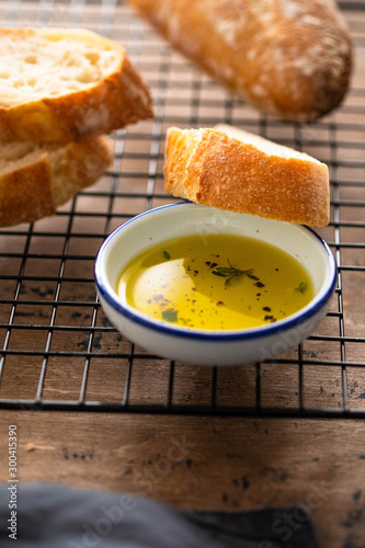 Freshly baked white bread with olive oil and herbs on wooden background.