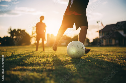 A boy kicking a ball with bare foot while playing street soccer football on the green grass field for exercise in community rural area under the twilight sunset Canvas Print