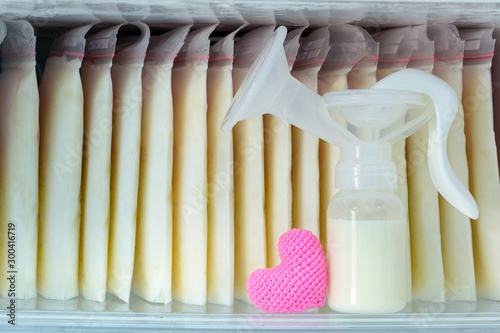 Stock of breast milk frozen in storage bags and a pump bottle for a new baby of family and pink heart with love in the freezer of refrigerator Fototapete