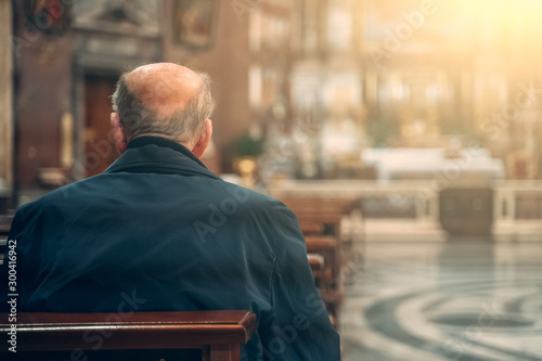 Elderly man prays while sitting on bench inside church, rear view.