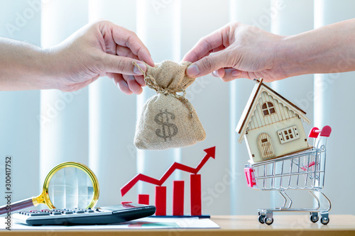Pinturas sobre lienzo  Businessman hand hold a money bag and home and red bar graph with growing value  in the office, agreement as business investment for real estate or loan contract for buy a house concept