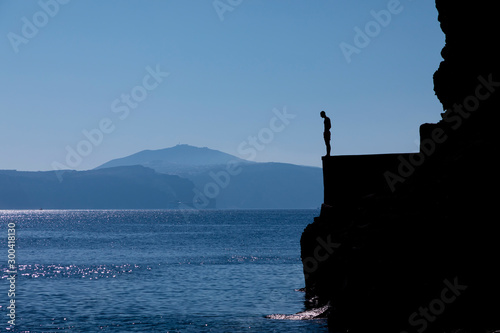 Fototapety, obrazy: Tourists jumping off a large rock ledge in Amoudi Bay on Santorini Island in Greece.